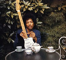 A color image of a man sitting at a table in the outdoors holding a black guitar.
