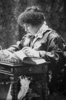 Black and white photograph of a woman seated at an ornate table writing notations in a book.