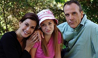 Susan Mayer - Susan poses with her first husband, Karl, and their daughter, Julie, while having a picnic in a park.