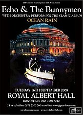 An poster advertising a concert with a black background and a picture of a circular building. Superimposed on the picture is a rowing boat with four men; two men are stood side-by-side at the back of the boat each holding an oar, the third man is sat in the centre of the boat and the fourth man is leaning over the front of the boat with his hand in the water. White text is on the poster at the top and the bottom giving details of the concert.