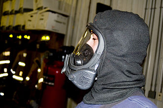 Self-contained breathing apparatus - A person wearing an MSA brand breathing mask with a Nomex hood on. This face piece attaches with a regulator to form a full SCBA.