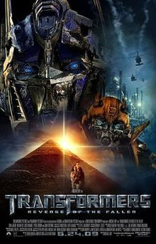 The faces of two robots stand atop a pyramid. A helicopter flies over an industrial facility on the right side of the image, and a young couple is seen in front of the pyramid, the film title and credits are on the bottom of the poster.