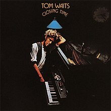 "A man leans against a piano in a dark room. The arched text above him reads ""Tom Waits Closing Time""."