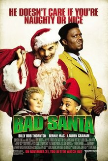 A scruffy dishevelled Santa Claus, standing beside a scowling man in a yellow suit, and a fat child and an Santa helper elf standing in front of them.