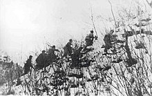 A group of soldiers climbing up a snow-covered hill
