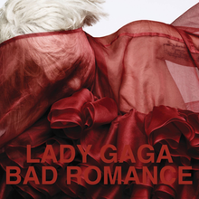 "Upper bust of a blond woman. She has short cropped hair. Her body and her face is covered by a red translucent cloth with intricate wrappings in the front. Over the image the words ""Lady Gaga"" and ""Bad Romance"" are written in red capital letters."