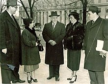 Five persons stand in heavy overcoats in front of an imposing federal building