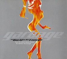 "Against a gray background lies a cutout of flames in the shape of a woman holding a gun. In front of the figure is the text ""Garbage - The World Is Not Enough - From the MGM motion picture The World Is Not Enough""."