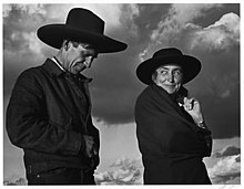 A black and white photograph shows Georgia O'Keeffe and Orville Cox wearing hats with the sky and clouds behind them.