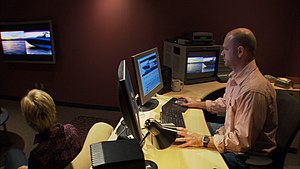 Video production -  A video editor operating an AVID video software editing system in an editing suite