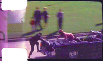 Zapruder film - Frame 371 showing Jacqueline Kennedy reaching out across the back of the presidential limousine as Secret Service agent Clint Hill climbs aboard.