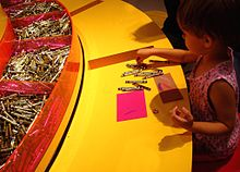 A young girl draws with Crayola crayons at the Crayola Experience