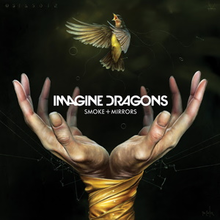 """Two hands bound by tape release a hummingbird into the air. The dark green background is littered with various lines and geometric shapes with numbers and symbols written into the top of the artwork. The words """"Imagine Dragons"""" and """"Smoke + Mirrors"""" are printed in white at the center of the artwork."""