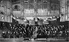 interior of a Victorian concert hall, showing the orchestra and conductor on the platform