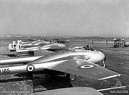 Row of single-engined fighter aircraft with twin tail booms, parked on airfield
