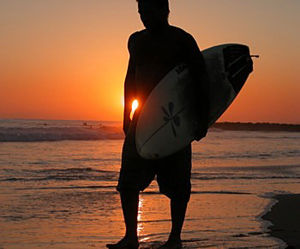 A surfer carrying his board.