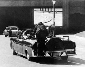 Ike Altgens - Altgens' seventh photograph, reproduced by newspapers around the world, shows the immediate aftermath of the shooting. Secret Service agent Clint Hill and Jacqueline Kennedy are seen in the foreground.