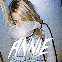 The cover of Anniemal featuring the word Annie at the bottom and showing Annie, a twentysomething blonde woman, with her arm covering her mouth