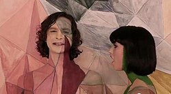Upper body shot of a man (left) and a woman turned towards him. The man is taller and has dark stragly hair. The woman has dark hair cut in a bob. Both have skin painted in coloured geometric designs. Both are singing. The backdrop has a similarly coloured design closely matching the design on the two people.