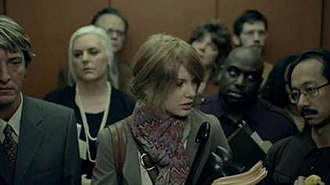 """Ours (song) - Swift in an elevator with co-workers in the music video for """"Ours""""."""