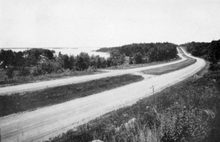 A black and white photo shows a smooth, gravel, divided roadway with a grass median. There are no safety features such as guardrails.