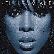 A close-up image of a woman's face covers the image. Her skin is blue and she is looking directly at the camera, with her face framed by her long black hair. Across the top in white text it reads KELLY ROWLAND (the name of the artist). On the line immediately below, in smaller text and aligned to the right, it reads HERE I AM (the name of the album).