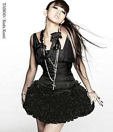 "A woman, dressed in a black dress with black-coloured accessories, posing towards the camera with blonde streaks in her hair. The text ""Koda Kumi"", and ""Taboo"" are placed on the upper-left side of the image."