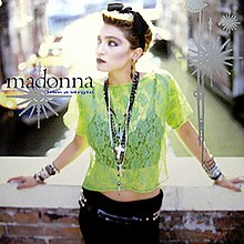 Madonna standing on a bridge wearing a light green see-through top and black pant.
