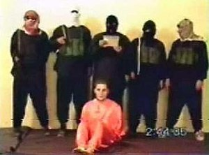 Abu Musab al-Zarqawi - American hostage Nick Berg seated, with five men standing over him. The man directly behind him, alleged to be Zarqawi, is the one who beheaded Berg.
