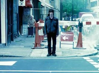 Bitter Sweet Symphony - A screenshot at the beginning of the music video showing Ashcroft, standing on a pavement. The video was noted as one of the most recognisable videos in the 90s.