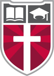 "Faith Academy's logo, the ""Shield of Faith,"" displaying a Christian cross and the school's motto."