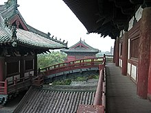 Several wooden buildings with grey tile roofs, connected by an arched bridge. A forest can be seen behind the buildings.
