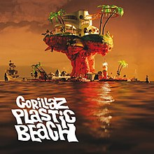"The cover of the third Gorillaz album ""Plastic Beach"". An artificial island rests on the ocean during a sunset. Apart from the base, it is mostly mushroom-shaped. It contains a few palm trees and small buildings. At the very top is a large white building with many windows. Other objects in and around the island include a ship, a buoy, a lighthouse and a crate. The view shows the opposite side of the island from the ""Experience Edition"" cover. In the lower left corner are the uppercase words ""Gorillaz Plastic Beach"" on separate rows. They are white and in a thick, wavy font."