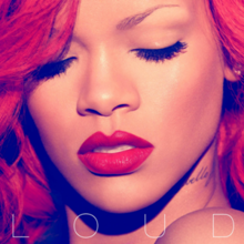 "A close up of Rihanna's face with long wavy red hair, both of Rihanna's eyes are closed and you can see her lips have red lipstick on them on her neck there is a tattoo that says ""Rebelle fleur"" but only parts of 'Rebelle' is visible."