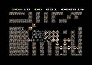 Boulder Dash - Rockford, left, drops a series of boulders on a series of butterflies. The butterflies explode into diamonds, which fall down the shafts. Commodore 64 version.