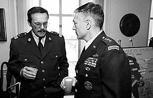 Generals Clark and Ćosić talking at a meeting
