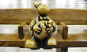 Life Underground - A portly figure of a well dressed man sitting on a platform level bench holding a moneybag as a train passes through the station. The bronze surface is polished by the hands of passersby.