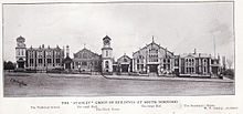 A black and white photograph showing the buildings built/designed by Stanley. From left to right they are the Technical School, the small Hall, the Clock Tower, the large Hall and the Secretary's House. They are seen from across the road, with fencing in front of the buildings.