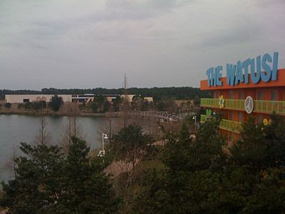 An incomplete Pop Century Legendary Years building can be seen across Hourglass Lake. The Generation Gap Bridge would have connected both halves of the resort.