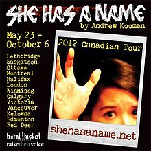 "A black square with the words ""SHE HAS A NAME"" in white letters at the top and an instant photograph below the words, depicting part of a face and a hand"