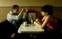 A small, square table with round edges against a tan wall. On the table there are coffee cups and a menu, with chairs on two sides, opposite each other. On the right sits a young, brunette woman with large earrings, fringe hair and a pink dress, who stirs the coffee. On the left sits a young man in a grey jumper, who gesticulates the act of punching with his hands.