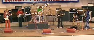 Five men are on stage with the man at left playing a guitar and facing to his left. The second man plays a bass guitar. The third man is behind his drum kit. The fourth man is playing a guitar and the last man is playing saxophone.