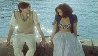 Two young people are sitting in front of a lake. The man is wearing a beige vest, a shirt and jeans tan, and a beard. He is looking to the woman. She is a brunette that is wearing a blue sweater, a bra with blue and white squares and a long white skirt.