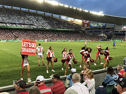 The Flames, the cheersquad for the St. George Illawarra Dragons, performing during an NRL match in 2018. Dragons cheerleaders.jpg