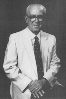 An elderly Jack Devine, seated with hand on lap, wearing a white suit jacket