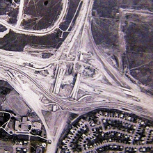 A bird's-eye view of a large highway interchange under construction. Several bridges are complete, but nothing is paved, aside from one highway crossing horizontally, which detours between the bridges.