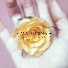 "An orange flower is held in the palm of a hand amid a purple background. In the middle, the word ""Madonna"" is written in white capital letters, with ""Bedtime Story"", also in capital letters and the same color, written below in smaller size."