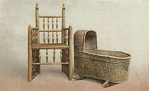 "Turned chair - The ""Brewster Chair"" (shown with a period wicker cradle) is at Pilgrim Hall Museum in Plymouth, Massachusetts."