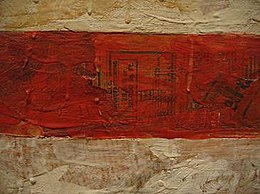 Detail of Flag (1954-55). Museum of Modern Art, New York City. This image illustrates Johns' early technique of painting with thick, dripping encaustic over a collage made from found materials such as newspaper. This rough construction is rarely evident in reproductions of the work as a whole.