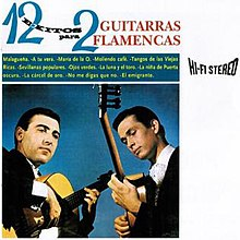 Two men in black suits playing flamenco guitars in front of a blue background